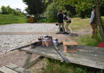 Tisch mit zwei Flinten vor drei Schützen